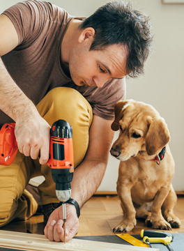 man with drill and a dog